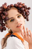 portrait of rustic blonde woman posing with grapes on head isolated on white