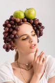 portrét rustikální blondýny pózující s hrozny a jablky na hlavě izolované na bílém