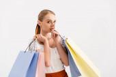 elegantní žena s nákupní tašky ukazující shh znamení izolované na bílém