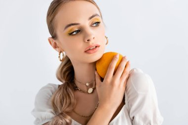 Elegant blonde woman posing with orange and looking away isolated on white stock vector