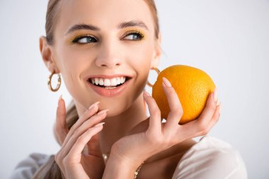 Cheerful elegant blonde woman holding orange and looking away isolated on white stock vector