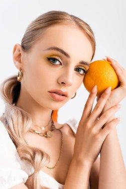 Elegant blonde woman posing with orange isolated on white stock vector