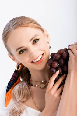 Rustic blonde woman posing with grapes isolated on white stock vector