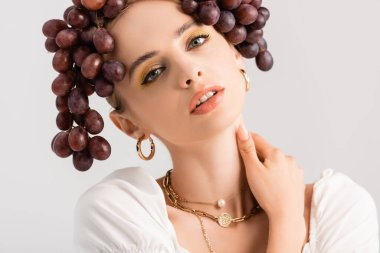 Portrait of rustic blonde woman posing with grapes on head isolated on white stock vector