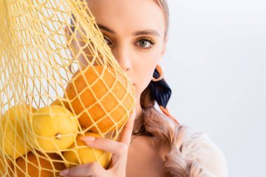 Rustic blonde woman posing with citrus fruits in yellow string bag in front of face isolated on white stock vector