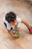 shora pohled na kudrnaté africké americké dítě hrající si s autíčky na dřevěné podlaze