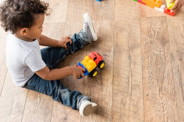 Overhead view of african american boy in jeans playing with toy truck on wooden floor stock vector