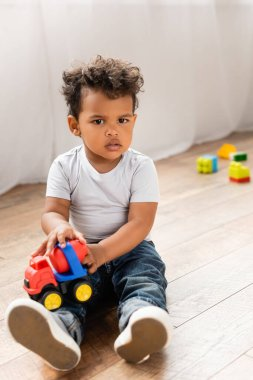 Serious african american kid in white t-shirt and jeans sitting on wooden floor with toy truck and looking at camera stock vector