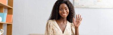 Horizontal image of african american woman waving hand while looking at camera stock vector