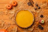vrchní pohled na dýňový koláč s podzimní výzdobou na dřevěném pozadí