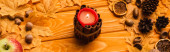 Photo burning candle with autumnal decoration on wooden background, panoramic shot
