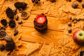 Photo burning candle with autumnal decoration on wooden background