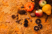 Photo top view of autumnal decoration and food scattered from wicker basket on golden foliage on wooden background