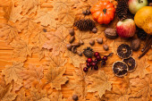 Photo top view of autumnal decoration and food on golden foliage on wooden background