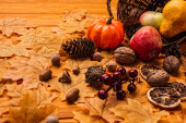 Photo autumnal decoration and food scattered from wicker basket on golden foliage on wooden background