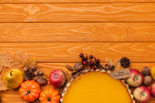 top view of thanksgiving pumpkin pie with autumnal decoration on wooden background