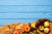 Fotografie top view of autumnal harvest in basket and foliage on blue wooden background