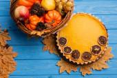 top view of autumnal harvest in wicker basket near pumpkin pie on blue wooden background