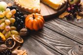 podzimní dekorace a dýňový koláč na hnědém dřevěném pozadí