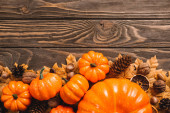 Photo top view of autumnal decoration and pumpkins on brown wooden background