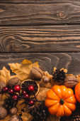 top view of autumnal decoration and pumpkin on brown wooden background