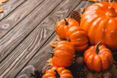 podzimní dekorace a dýně na hnědém dřevěném pozadí