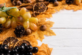 selective focus of autumnal decoration and grapes on white wooden background
