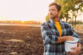 rančer v kostkované košili drží vědro, zatímco stojí na oraném poli ve slunečním svitu