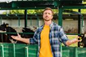 rančer v kostkované košili dívá na kameru, zatímco stojí s otevřenou náručí v blízkosti kravína