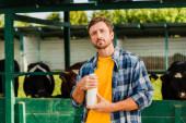 Rancher im karierten Hemd mit einer Flasche frischer Milch, während er in die Kamera in der Nähe des Kuhstalls blickt