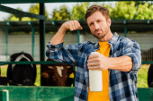 selektiver Fokus eines Bauern im karierten Hemd, der eine Flasche Milch hält und gleichzeitig Macht demonstriert