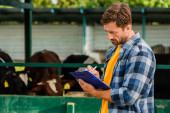 Rancher in kariertem Hemd schreibt auf Klemmbrett in der Nähe von Kuhstall auf Bauernhof