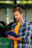 concentrated farmer in plaid shirt writing on clipboard on farm