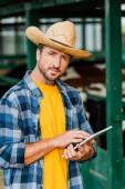 farmář v slamáku a kostkované košili pomocí digitálního tabletu při pohledu na fotoaparát