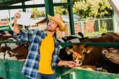 farmář v kostkované košili a slamáku se selfie s krávami na digitálním tabletu