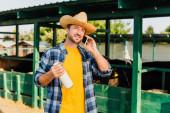 farmář v kostkované košili a slamák mluví na smartphone, zatímco drží láhev mléka