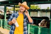 farmář v kostkované košili a slamák klobouk drží láhev čerstvého mléka, zatímco mluví na smartphone