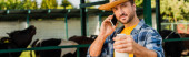 panoramic concept of farmer in straw hat and plaid shirt holding bottle of milk while talking on mobile phone