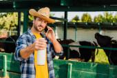 Bauer in kariertem Hemd und Strohhut hält beim Telefonieren eine Flasche Milch in der Hand