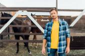 rančer v kostkované košili stojí poblíž ohrady s koňmi a dívá se do kamery