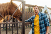 Photo farmer in plaid shirt looking at camera while touching head of brown horse in corral