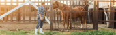 Photo panoramic concept of rancher in plaid shirt and rubber boots touching brown horse in corral