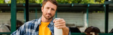 Horizontal image of farmer in checkered shirt holding bottle of fresh milk and looking at camera stock vector