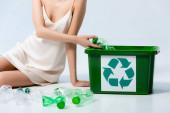 ořezaný pohled na ženu v hedvábných šatech házení plastové láhve v koši s recyklační značkou na bílém, koncept ekologie