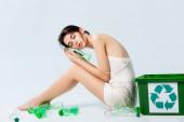 bruneta žena se zavřenýma očima v hedvábných šatech sedí v blízkosti plastových lahví a koše s recyklačním nápisem na bílé, ekologie koncept