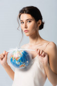 young brunette woman holding plastic bag with globe and looking at camera isolated on white, ecology concept
