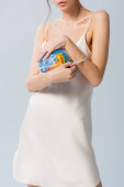 cropped view of young woman in silk dress holding plastic bag with globe isolated on white, ecology concept
