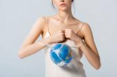 částečný pohled na model v hedvábných šatech s plastovým sáčkem s glóbem izolovaným na bílé, koncept ekologie