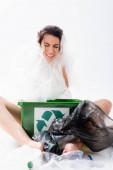 bosá žena s migrénou zabalená v igelitovém sáčku sedící u popelnice s nápisem recyklace na bílém, ekologický koncept