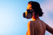 Photo brunette woman in gas mask looking at camera on blue